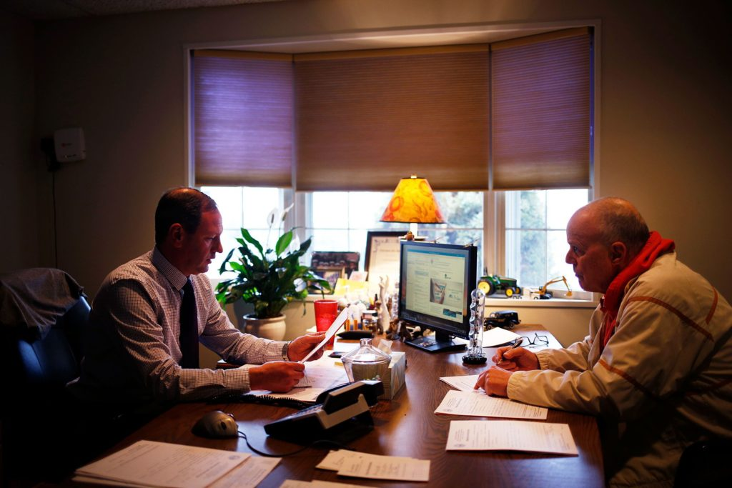 Owner Mike Stringer, left, meets with with New Hampshire Assistant Deputy Medical Examiner Mike Raymond to sign permissions for cremations at Stringer Funeral Home in Claremont, N.H., on Tuesday, April 9, 2019. Every cremation requires approval from a medical examiner. The funeral home now has a crematorium on site to make the process much easier. (Valley News - Joseph Ressler) Copyright Valley News. May not be reprinted or used online without permission. Send requests to permission@vnews.com.