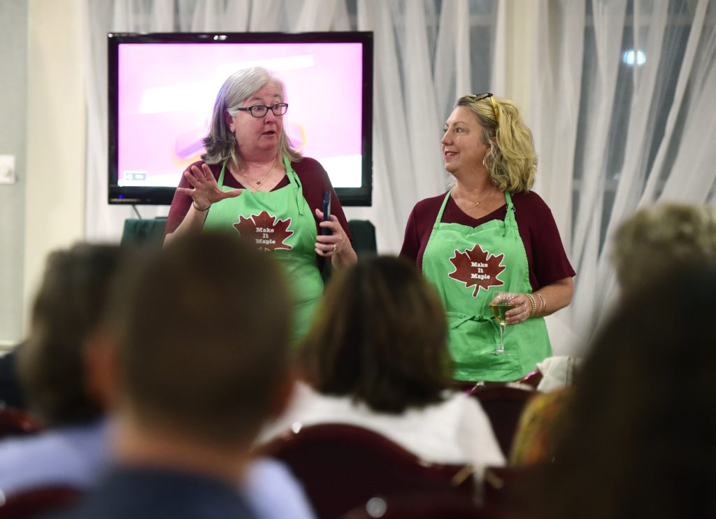 Sue Aldrich, left, and Paulette Fiorentino, both of Montpelier, Vt., explain some of the behind-the-scene details of their time competing on The Great Food Truck Race during a screening party for the opening episode at the Capital Plaza in Montpelier, Vt. on June 9, 2019. The reality program airs on The Food Network and the pair, along with Aldrich's son, Charlie, competed as the Make It Maple team.