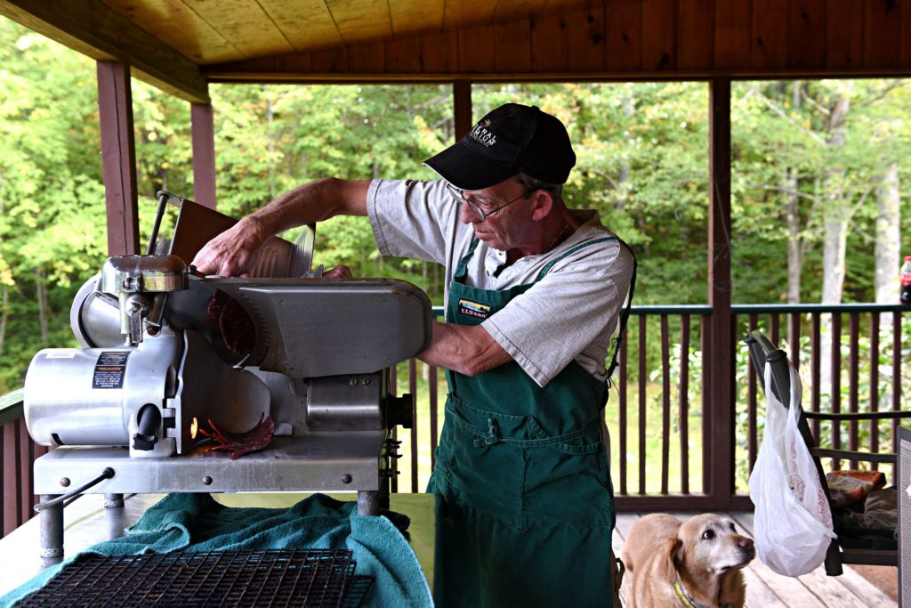 Sean Bohman, of Warner, N.H., slices frozen buffalo livers at his home on Tuesday, Sept. 24, 2019. Bohman and his wife dehydrate organ meat to make 3 Biddy's Pet Treats. (Valley News - Jennifer Hauck) Copyright Valley News. May not be reprinted or used online without permission. Send requests to permission@vnews.com.