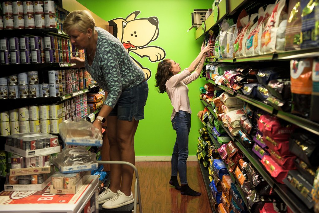 Unleashed owner, Penny Murano, left, and employee Dakota Page, right, shelve stock from a shipment at the store in New London, N.H., Wednesday, Sept., 25, 2019. Murano bought Unleashed in 2006 and has refined the store into a dog and cat supply boutigue with a grooming service. (Valley News - James M. Patterson) Copyright Valley News. May not be reprinted or used online without permission. Send requests to permission@vnews.com.