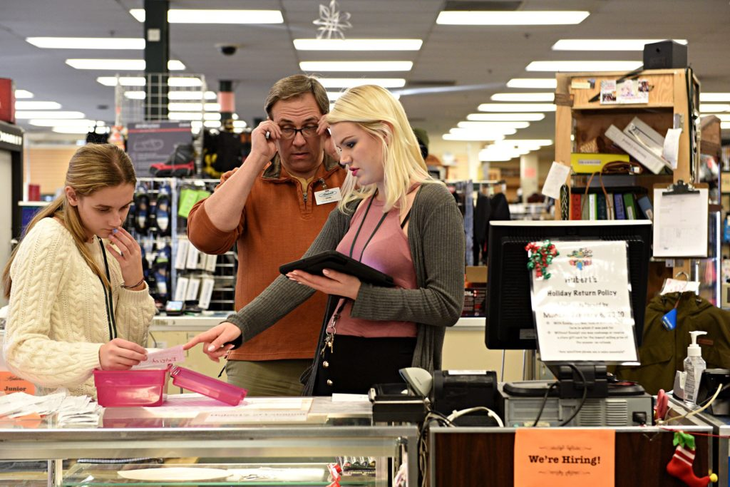 Hubert's manager John Tostenson works with employees Sydney Gonyea, left, and Hannah Small at the register in Lebanon, N.H., on Saturday, Dec. 28, 2019. (Valley News - Jennifer Hauck) Copyright Valley News. May not be reprinted or used online without permission. Send requests to permission@vnews.com.