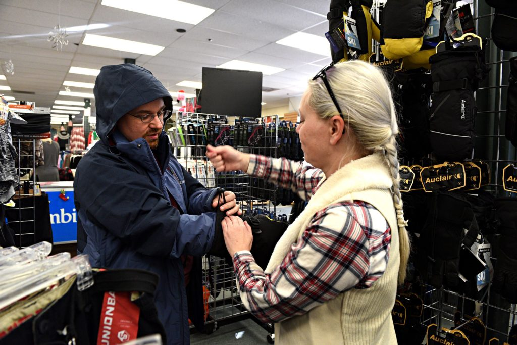 Amber Grantham, of Sunapee, N.H., helps her friend Dustin Springer, of Claremont, N.H., into new ski gear at Hubert's in Lebanon, N.H., on Saturday, Dec. 28, 2019. Grantham is teaching Springer to ski, starting with helping him pick out winter gear. (Valley News - Jennifer Hauck) Copyright Valley News. May not be reprinted or used online without permission. Send requests to permission@vnews.com.