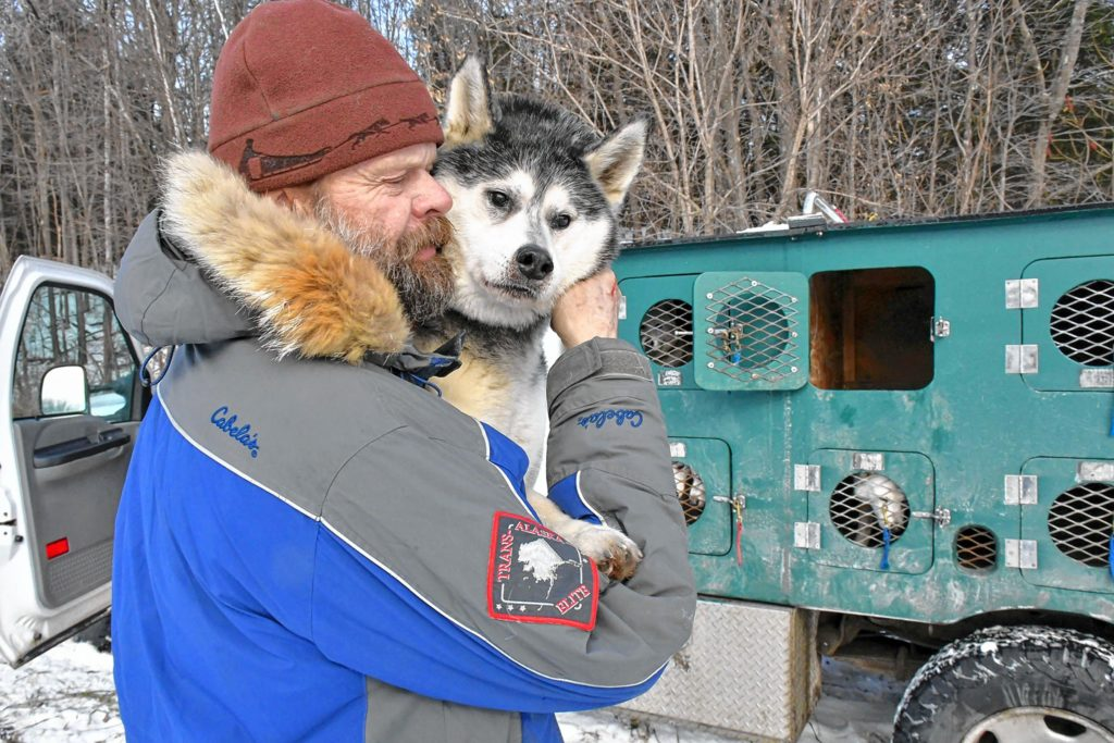 Alex MacLennan of Windsor, Vt., who is co-owner of Braeburn Siberians, pauses to spend a moment with Anakin, the patriarch of his sled dog team while lifting him down from his truck kennel in Claremont, N.H., on Sun. Dec. 22, 2019. Anakin is the grandfather of most of MacLennan's dogs and though nearly blind still likes to pull sleds while being guided by the dog harnessed next to him. (Rick Russell photograph)