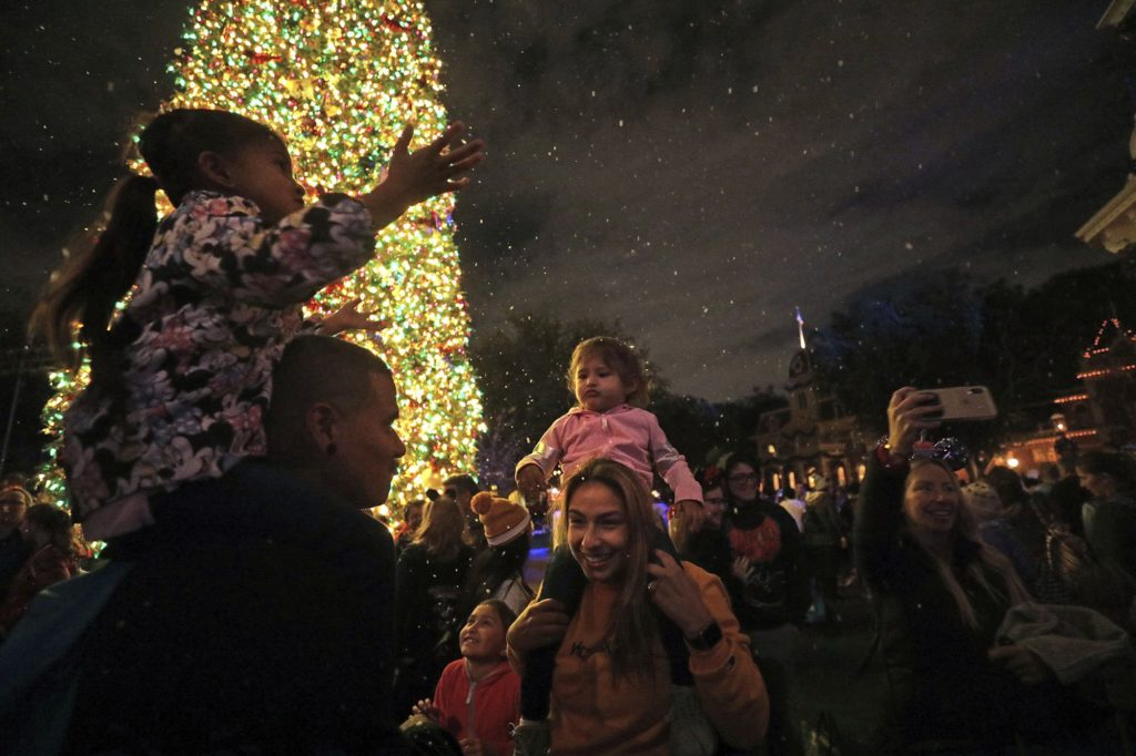 Tino Liquigan, left, and wife Raquel with their daughters amid the falling 'snow' on Disneyland's Main Street on Nov. 21, 2019 in Anaheim, Calif. (Myung J. Chun/Los Angeles Times/TNS)