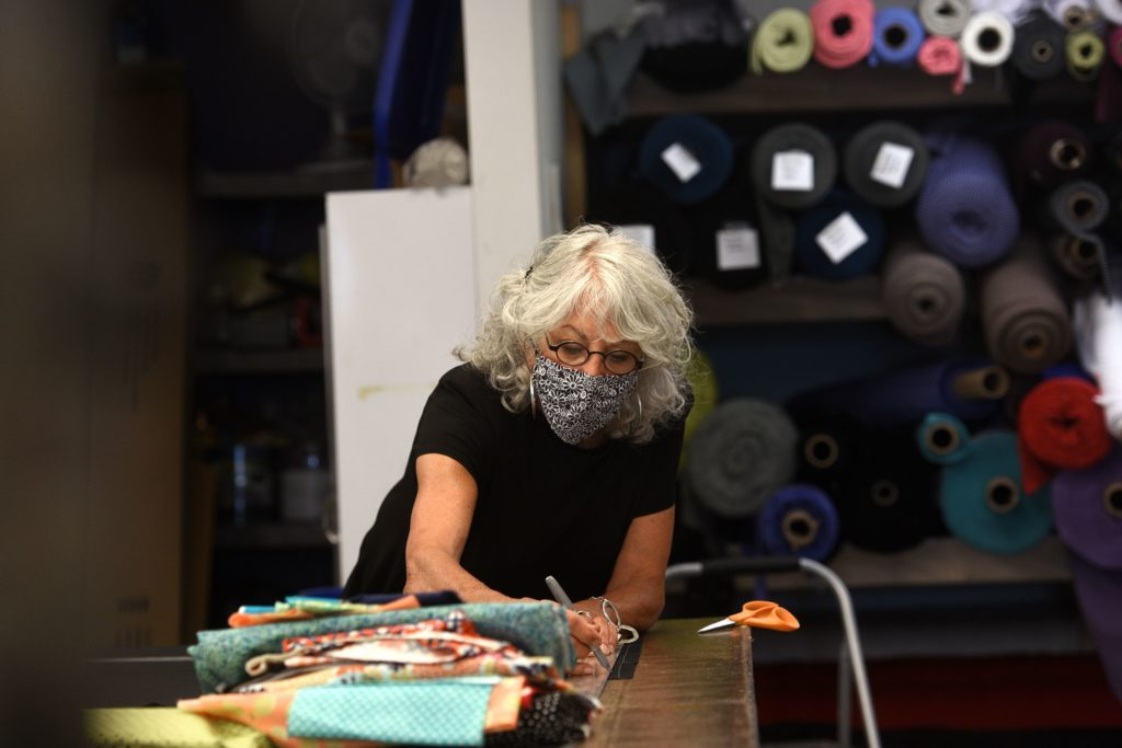 Joan Ecker, co-owner of Fat Hat Clothing Co., cuts material for masks on Wednesday, July 1, 2020, in Quechee, Vt. The company has made 5,000 cloth masks during the COVID-19 pandemic. (Valley News - Jennifer Hauck) Copyright Valley News. May not be reprinted or used online without permission. Send requests to permission@vnews.com.