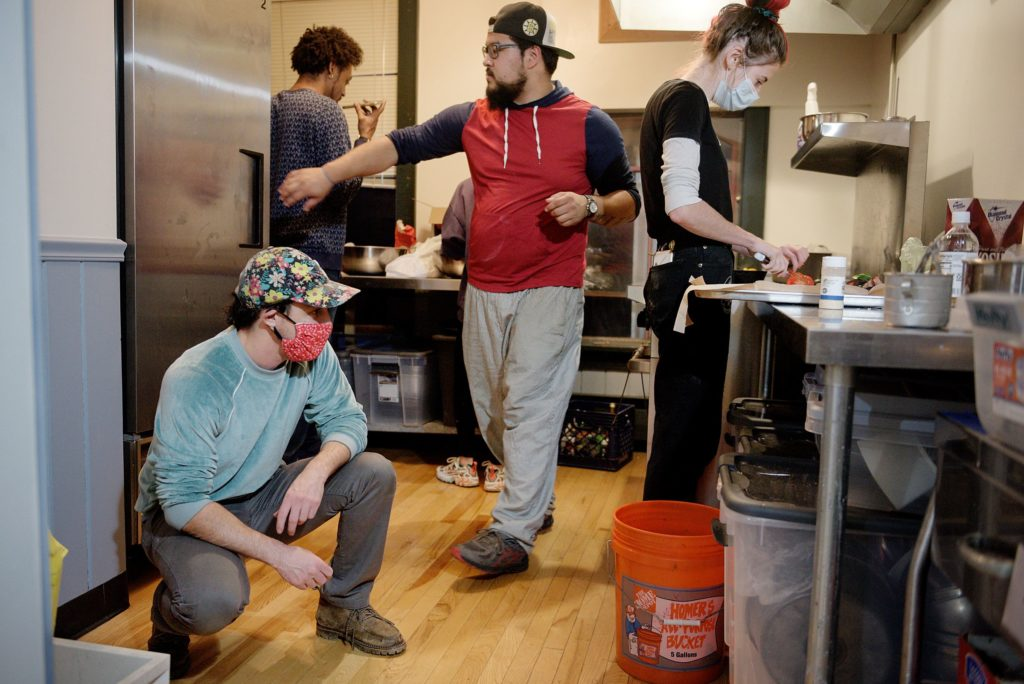 "Jesse Plotsky, co-owner of Babes Bar, left, looks for a cake pan as Tre Groves, top left, Tristan Brown, middle, and Grace Dorman, right, prepare a meal at the Arnold Block test kitchen in Bethel, Vt., Wednesday, Oct. 8, 2020. The group is developing a menu for a food trailer they are preparing to open with Babes as the parent business. ""I am not remarkable in any particular way,"" said Plotsky about his activism. ""I see my role as the holder of space. I'm basically here to do what is asked of me, knowing the power that I hold as a business owner and as a white person."" (Valley News - James M. Patterson) Copyright Valley News. May not be reprinted or used online without permission. Send requests to permission@vnews.com."
