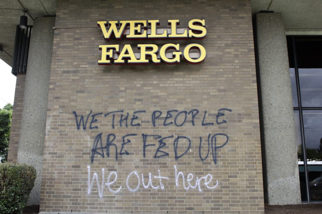 Graffiti covers the exterior of a Wells Fargo bank on Wednesday, July 1, 2020, in a historically Black neighborhood in Portland, Ore., that has been the scene of violent clashes with police in recent days. Thousands of protesters in the liberal and predominantly white city have taken to the streets peacefully every day for more than five weeks to decry police brutality, but recent violence by smaller groups is creating a deep schism in the protest movement. As demonstrations enter...