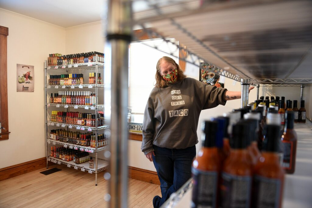 Roberta Parker, who co-owns Angry Goat Pepper Co. with her husband, looks over the inventory at their retail store in White River Junction, Vt., on Friday, Jan. 8, 2020. ( Valley News - Jennifer Hauck) Copyright Valley News. May not be reprinted or used online without permission. Send requests to permission@vnews.com.