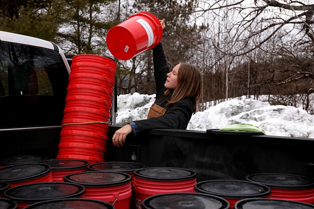 Lydia Dickey, 12, unloads clean compost buckets for customers while helping her father on the route in Woodstock, Vt., on Jan. 14, 2021. Nordic Waste Service's We Recycle Food program offers weekly curbside, drop-off and commercial services for composting and currently has over 200 clients across the Upper Valley. (Valley News - Geoff Hansen) Copyright Valley News. May not be reprinted or used online without permission. Send requests to permission@vnews.com.