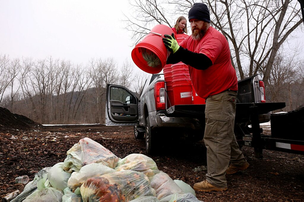 Joshua Dickey, who is General Manager for Nordic Waste Services in Lebanon, N.H., drops a load of compost with his daughter Lydia's help at the landfill in West Lebanon on Jan. 14, 2021. The company's We Recycle Food program offers weekly curbside, drop-off and commercial services for composting. (Valley News - Geoff Hansen) Copyright Valley News. May not be reprinted or used online without permission. Send requests to permission@vnews.com.