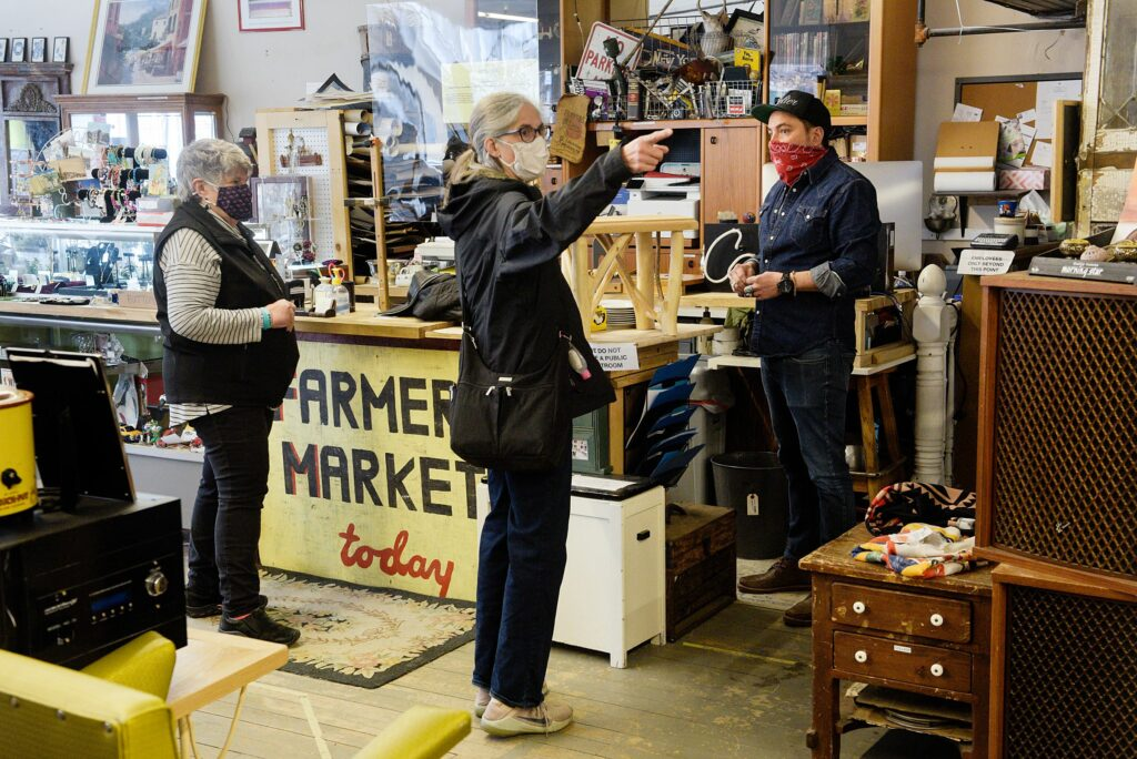 """Marge Audet, of Bradford, left, and Cindy Perry, of Thetford, middle, both admired pieces of natural wood furniture by the same maker at Consign and Design owned by Chris Lin, right, in West Lebanon, N.H., Friday, March 26, 2021. Lin sells antiques and items he has collected while """"picking"""" throughout New England on the ground floor of the store and has two floors of consignment booths above. """"I'm finding everything I want today,"""" said Perry, who was outfitting a house she owns for short-term vacation rentals. """"I'm getting what I need without shopping online. I'm sick of shopping online."""" (Valley News - James M. Patterson) Copyright Valley News. May not be reprinted or used online without permission. Send requests to permission@vnews.com."""