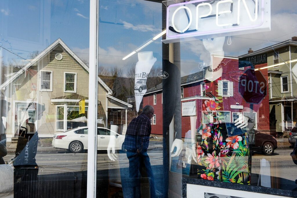 Buildings on Main Street in West Lebanon, N.H., are reflected in the windows of Consign and Design, a three-floor second-hand store, Friday, March 30, 2021. (Valley News - James M. Patterson) Copyright Valley News. May not be reprinted or used online without permission. Send requests to permission@vnews.com.