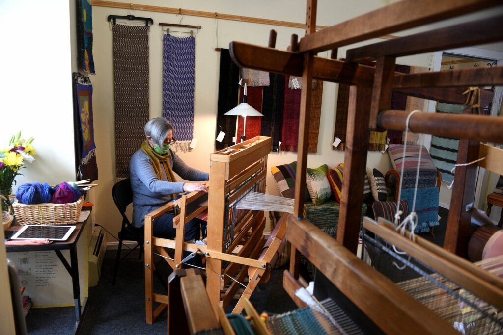 Vassie Sinopoulos works on one of her looms at her studio in Woodstock, Vt., on April 2, 2021. Sinopoulos sometimes uses recycled fabric in her pieces. ( Valley News - Jennifer Hauck) Copyright Valley News. May not be reprinted or used online without permission. Send requests to permission@vnews.com.