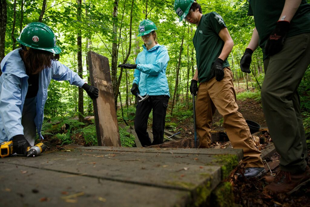 Vermont Youth Conservation Corps members, from left, Beatrix Garza, 15, of Woodstock, Vt., Chloe Masillo, 15, of Pittsfield, Vt., Ben Johnsen, 15, of Pomfret, Vt., and Andries Morin, 16, of Pittsfield, Vt., work to replace a footbridge near the Prosper Trail trailhead at Marsh-Billings-Rockefeller National Historic Park in Woodstock, Vt., on Tuesday, June 22, 2021. VYCC hires young people, ages 15-26, to do farm and conservation work throughout the state to help them gain leadership and career skills while engaging with Vermont's natural environment. (Valley News / Report For America - Alex Driehaus) Copyright Valley News. May not be reprinted or used online without permission. Send requests to permission@vnews.com.