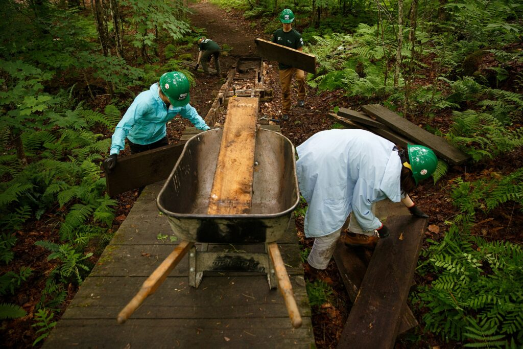 Vermont Youth Conservation Corps members, from left, Chloe Masillo, 15, of Pittsfield, Vt., Andries Morin, 16, of Pittsfield, Vt., Ben Johnsen, 15, of Pomfret, Vt., and  Beatrix Garza, 15, of Woodstock, Vt., work to replace a footbridge near the Prosper Trail trailhead at Marsh-Billings-Rockefeller National Historic Park in Woodstock, Vt., on Tuesday, June 22, 2021. (Valley News / Report For America - Alex Driehaus) Copyright Valley News. May not be reprinted or used online without permission. Send requests to permission@vnews.com.
