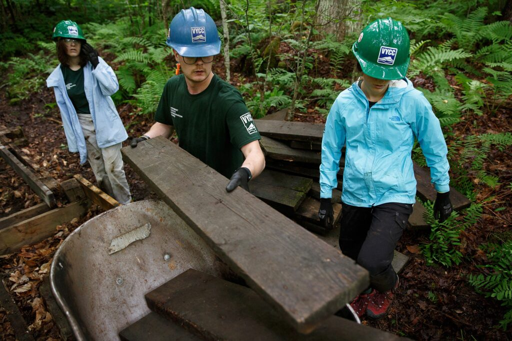 From left, Beatrix Garza, 15, of Woodstock, Vt., conservation crew leader Sawyer Connolly, of Enfield, N.H., and Chloe Masillo, 15, of Pittsfield, Vt., with Vermont Youth Conservation Corps replace a footbridge near the Prosper Trail trailhead at Marsh-Billings-Rockefeller National Historic Park in Woodstock, Vt., on Tuesday, June 22, 2021. The crew is tearing out the decaying boards and replacing them with pressure-treated wood. (Valley News / Report For America - Alex Driehaus) Copyright Valley News. May not be reprinted or used online without permission. Send requests to permission@vnews.com.