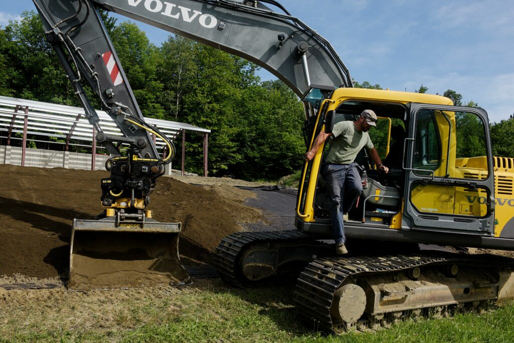 Ben Canonica, of Chelsea, steps down from his excavator after spreading a layer of topsoil on a septic system he is building as part of a new home for a client in Tunbridge, Vt., Friday, June 25, 2021. (Valley News - James M. Patterson) Copyright Valley News. May not be reprinted or used online without permission. Send requests to permission@vnews.com.