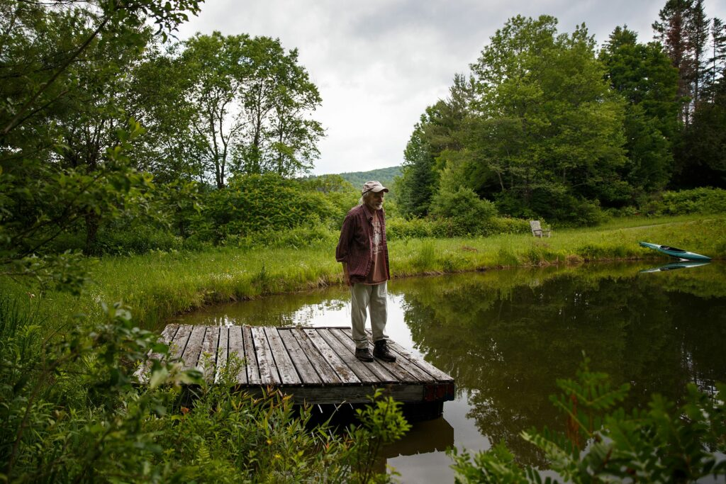 Tim Matson stands on the dock of the pond at his home in Strafford, Vt., on Monday, June 28, 2021. Matson designed the pond in the 1970s and swims in it every day in the summer. (Valley News / Report For America - Alex Driehaus) Copyright Valley News. May not be reprinted or used online without permission. Send requests to permission@vnews.com.