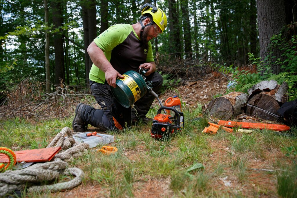 Matt Gray, of Goshen, N.H., refills a chainsaw with gas during a Chippers, Inc. tree removal job at a home in Hanover, N.H., on Wednesday, June 30, 2021. (Valley News / Report For America - Alex Driehaus) Copyright Valley News. May not be reprinted or used online without permission. Send requests to permission@vnews.com.